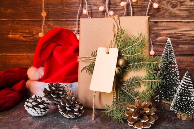 Weihnachtshut nahe geschenkbox verzierte den tannenzweig mit aufkleber
