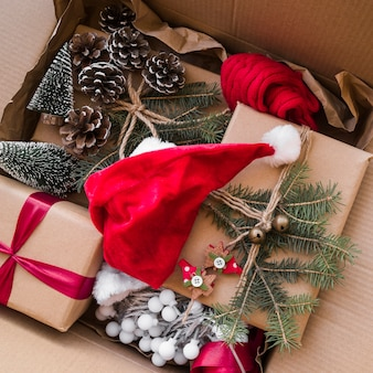 Weihnachtshut nahe geschenkboxen verzierte tannenzweige in der pappschachtel