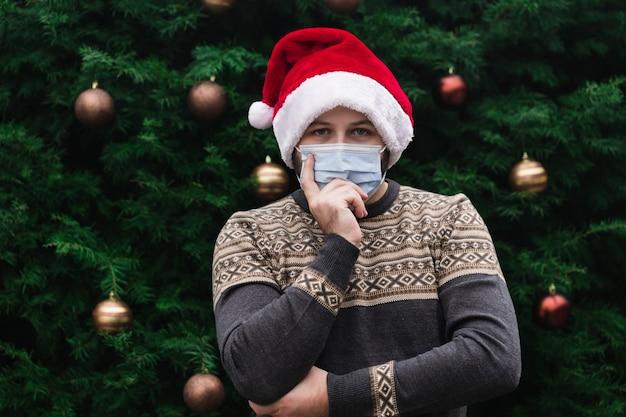 Weihnachtsidee. schließen sie herauf porträt des mannes, der einen weihnachtsmannhut, weihnachtspullover und medizinische maske mit emotion trägt. vor dem hintergrund eines weihnachtsbaumes. coronavirus pandemie