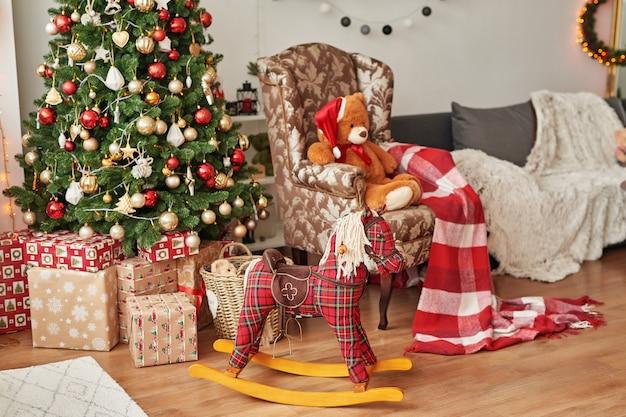 Weihnachtsinnenraum des kinderzimmers weihnachten in der kindertagesstätte. schaukelpferd und weiches spielzeug betreffen hintergrund des weihnachtsbaums.