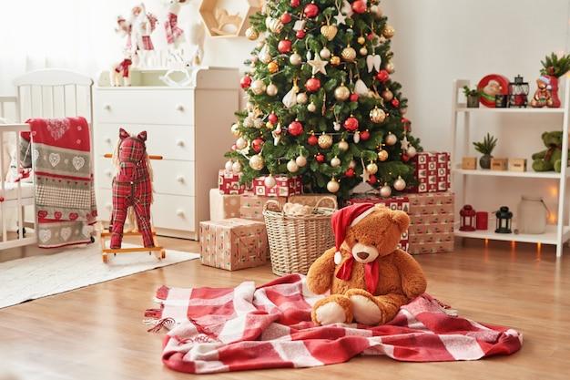 Weihnachtsinnenraum des kinderzimmers weihnachten in der kindertagesstätte. weiches spielzeug betreffen hintergrund des weihnachtsbaums