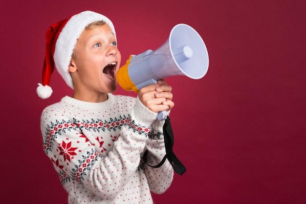 Weihnachtsjunge, der durch megaphon schreit