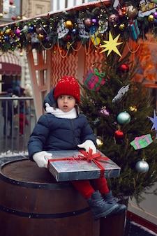 Weihnachtsjunge ein kind in warmen kleidern hält ein geschenk und sitzt auf einem fass neben einem weihnachtsbaum in moskau