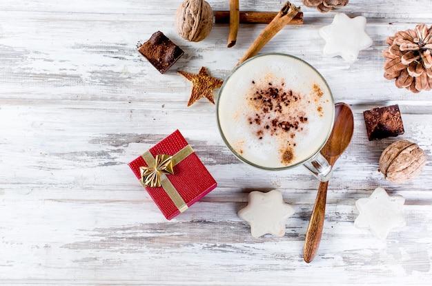 Weihnachtskaffee mit milch, gewürzen oder heißem kakao, tannenzapfen