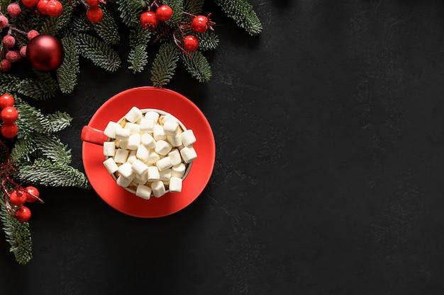 Weihnachtskaffee urlaub rote dekorationen immergrüne nobilis zweige und kugeln auf schwarz