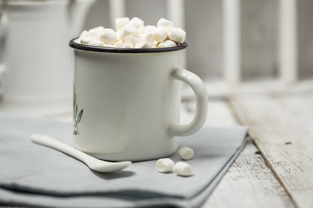 Weihnachtskakaogetränk. schokoladen-kakao-getränke mit marshmallows im weißen weihnachtsbecher auf grauer wand. traditionelles heißgetränk, festlicher cocktail zu weihnachten oder neujahr