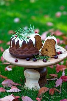 Weihnachtskaramellkuchen, cutaway, dekoriert mit weißer schokolade, preiselbeeren und rosmarin auf einem holzständer zwischen herbstblättern. festliche backwaren. weicher selektiver fokus. vertikal