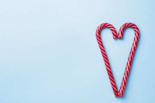 Weihnachtskaramellstockherz formte auf einen blauen pastell. feiertags-festliche feiergrußkarte. mit copyspace zum hinzufügen von text.