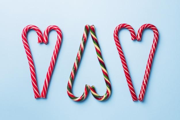 Weihnachtskaramellstockherz formte auf einen blauen pastell. feiertags-festliche feiergrußkarte.