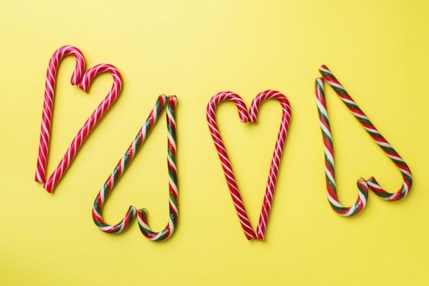 Weihnachtskaramellstöcke auf einem gelb. feiertags-festliche feiergrußkarte mit copyspace zum hinzufügen des textes.