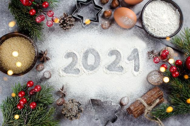 Weihnachtskarte. 2021 text aus mehl mit backzutaten - eier, brauner zucker, zimt und festliche weihnachtsdekoration auf dem tisch.