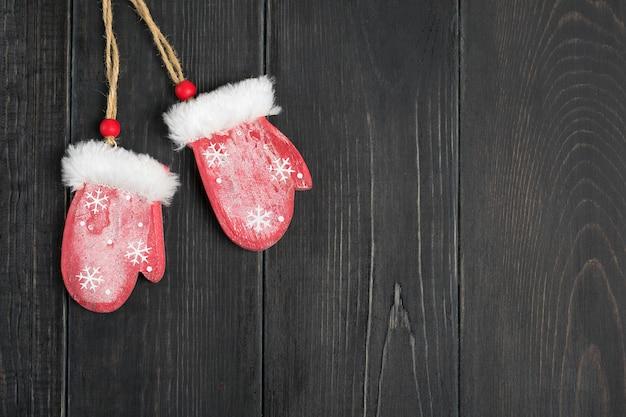 Weihnachtskarte dekor-rote handschuhe des neuen jahres auf hölzerner hintergrundebene legen rustikales s