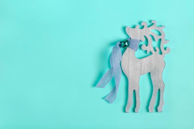Weihnachtskarte. dekorativer hölzerner hirsch des neuen jahres mit einem schal und einer glocke um den hals auf blau