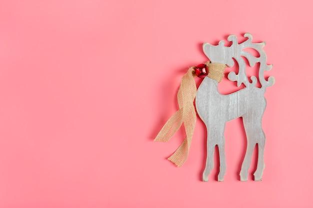 Weihnachtskarte. dekorativer hölzerner hirsch des neuen jahres mit einem schal und einer glocke um den hals auf rosa