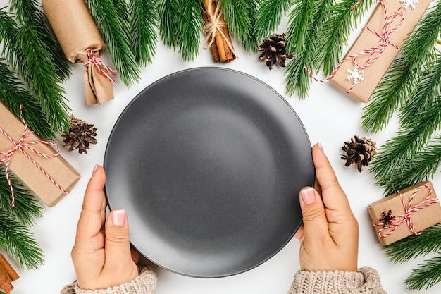Weihnachtskarte für restaurantrahmen aus tannenzweigen und frauenhänden mit einem leeren schwarzen teller