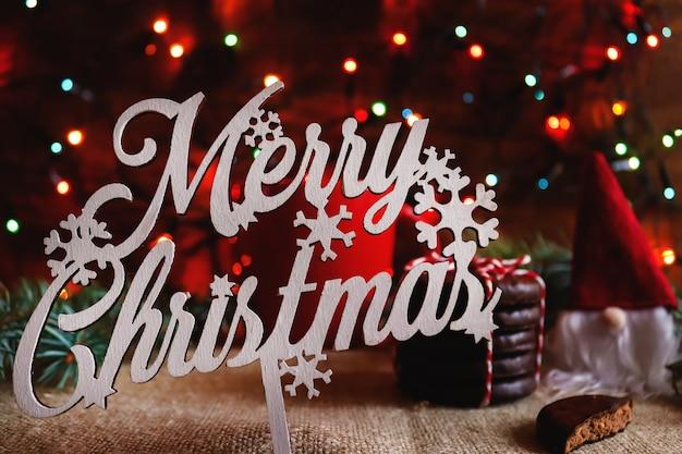 Weihnachtskarte im hygge-stil unscharfer hintergrund mit bokeh-schokoladenkeksen und kleinem gnom