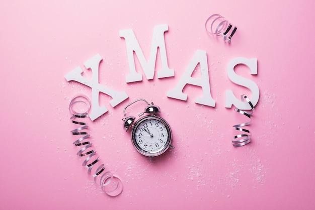 Weihnachtskarte mit buchstaben und uhr auf dem rosa hintergrund. weihnachtskonzept, ansicht von oben nach unten
