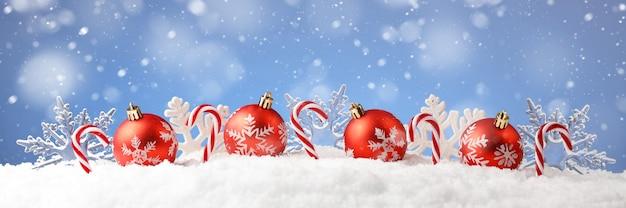 Weihnachtskarte mit dekorativen kugeln, süßigkeiten und schneeflocken auf schnee