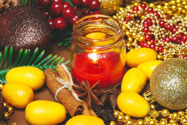 Weihnachtskarte mit einer kerze, christbaumschmuck, zimt und japanischer orange