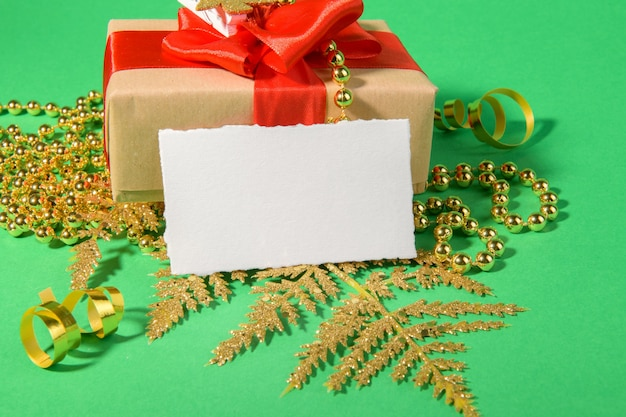 Weihnachtskarte mit geschenk goldene festliche dekoration auf einem grünen hintergrund.