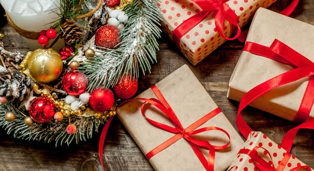 Weihnachtskarte mit geschenkbox und spielzeug auf einem holzhintergrund.