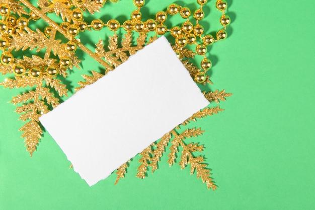 Weihnachtskarte mit goldener festlicher dekoration auf einem grünen hintergrund.