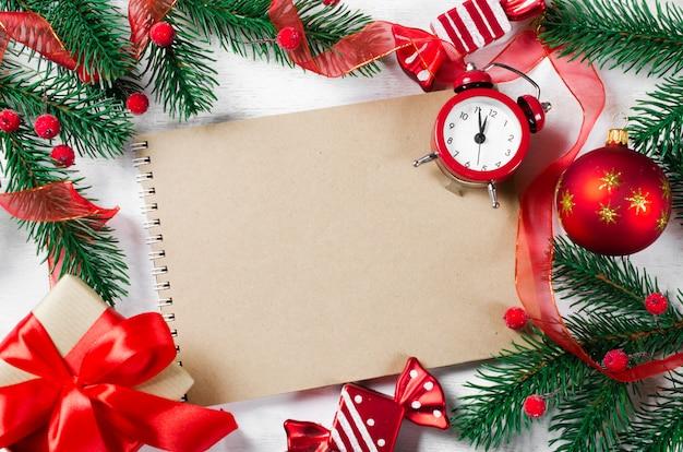 Weihnachtskarte mit leerem notizbuch und uhr.