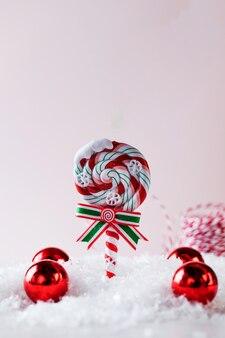 Weihnachtskarte mit lutscher und roten kugeln im schnee