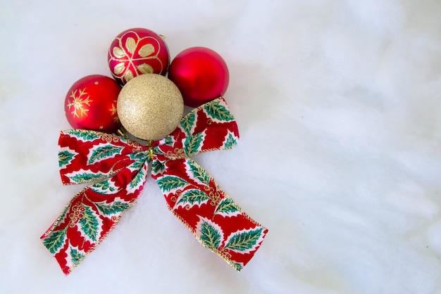 Weihnachtskarte mit roten und goldenen bällen und roter und grüner gleichheit auf schnee