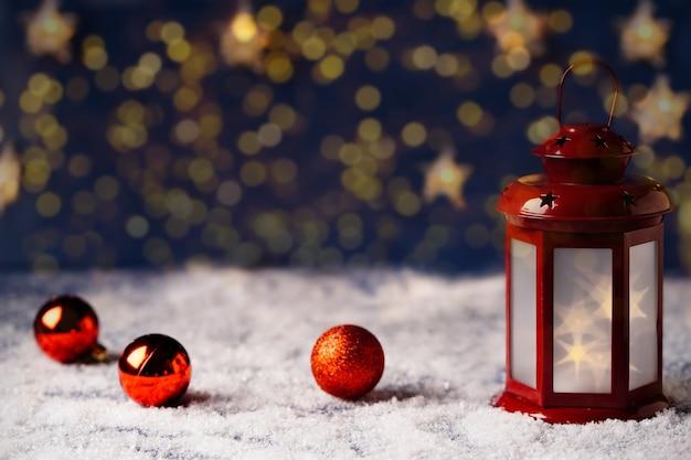 Weihnachtskarte mit roter laterne mit sternen auf goldenem bokeh