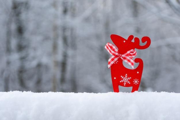 Weihnachtskarte mit schnee, schneeflocken, rotwild auf einem unscharfen natürlichen hintergrund. frohes neues jahr, festliche stimmung. winterhintergrund. speicherplatz kopieren.