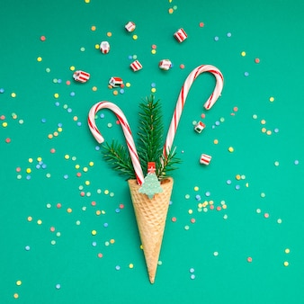 Weihnachtskarte mit zuckerstangen im waffelkegel