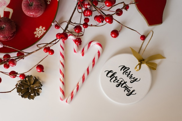 Weihnachtskarte, neujahr flach zu legen. spielen sie auf dem weihnachtsbaum, der süßigkeit und den roten beeren auf der niederlassung