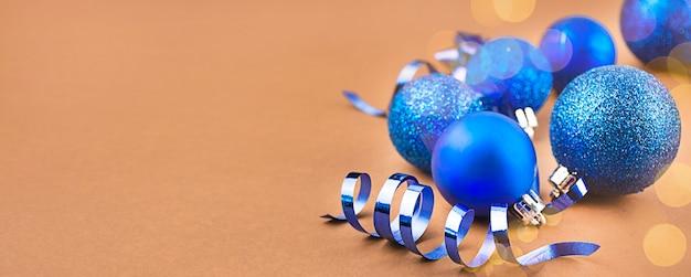 Weihnachtskarte von blauen kugeln auf einem braunen hintergrund mit höhepunkten. weihnachtsferien zusammensetzung.
