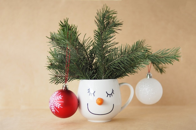 Weihnachtskartenbecher mit dem gesicht eines schneemanns mit tannenzweigen und weihnachtsschmuck auf handwerklichem hintergrund.