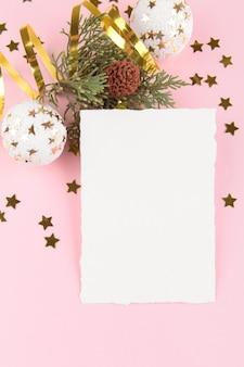 Weihnachtskartenschablone mit tannenzweigen und goldenen sternen und festlicher dekoration auf einem rosa pastellhintergrund.