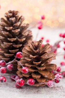 Weihnachtskegel mit roten beeren auf einem bokehhintergrund.
