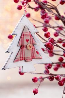 Weihnachtskegel mit roten beeren auf einem bokehhintergrund
