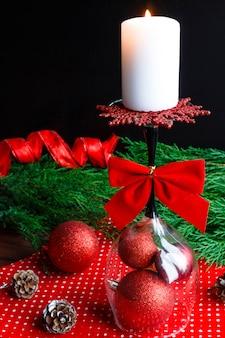 Weihnachtskerze auf umgekehrtem glas, fichtenzweigen und weihnachtsdekorationen desi