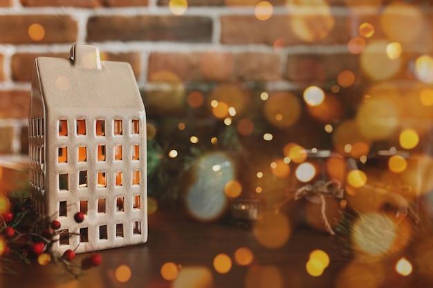 Weihnachtskerze in form von haus oder haus verschwommene tannenbaumlichter