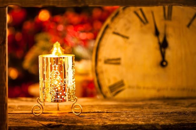 Weihnachtskerze und vintage-uhr gegen lichter verschwommenen hintergrund