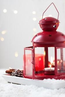 Weihnachtskerzen mit tannenzapfen, laterne, weihnachtsdekoration und schnee, winter oder ferienkonzept