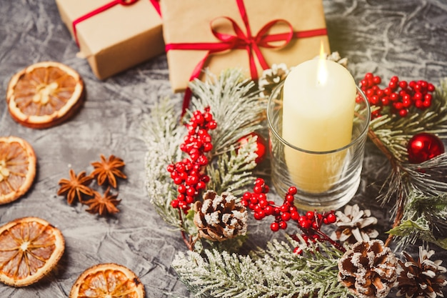 Weihnachtskerzen und -verzierungen über konkretem hintergrund mit lichtern.
