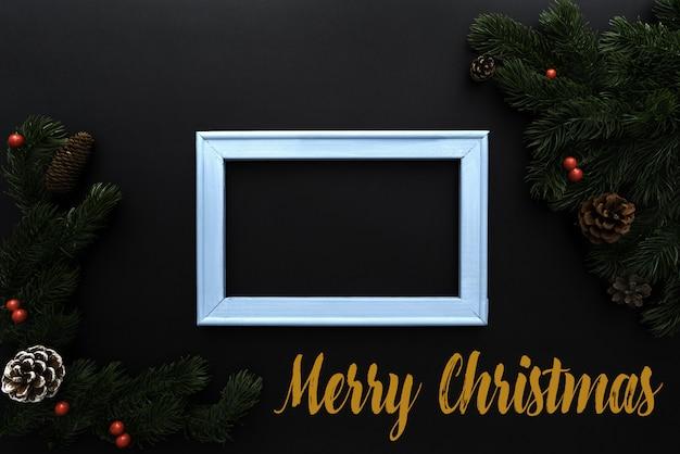 Weihnachtskiefer und fotorahmen mit weihnachtsdekoration auf schwarzem hintergrund