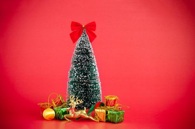 Weihnachtskiefernabdeckung mit dem schnee, der mit weihnachtsverzierungen über rotem hintergrund verziert