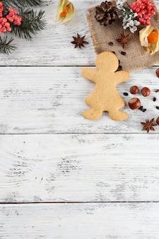 Weihnachtskiefernzweig mit gewürzen und lebkuchen auf farbigem holzhintergrund
