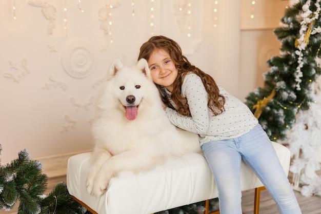 Weihnachtskind mädchen umarmen hund samojeden zu hause