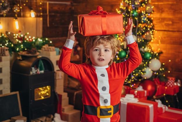 Weihnachtskind mit geschenkbox über dem kopf glückliches kind mit weihnachtsgeschenk neujahr weihnachtskon...