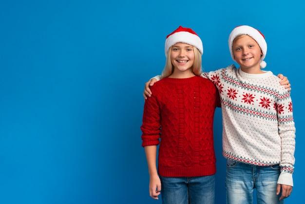 Weihnachtskinder, die mittleren schuss umarmen