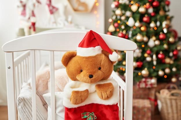Weihnachtskinderzimmer, weihnachtsdekoration im kinderzimmer, kinderspielzimmer für neujahr dekoriert, weißes kinderzimmer. weihnachtsspielwaren und -geschenke im schlafzimmer der kinder, weißes bett mit weichen spielwaren